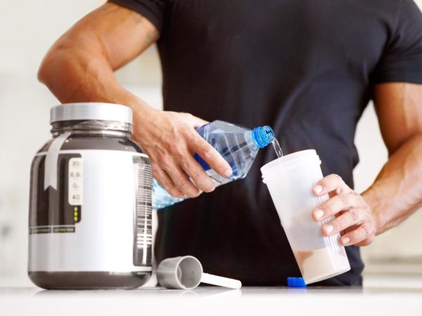 Cropped image of a bodybuilder making himself a protein shake