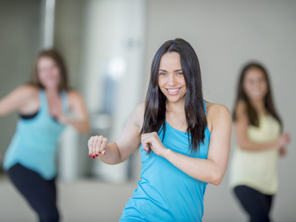 A multi-ethnic group of young adult women are at the gym taking a dance fitness class together. They are moving to the music and are smiling while looking at the camera.