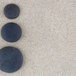 Three black zen stones at left side of sand background