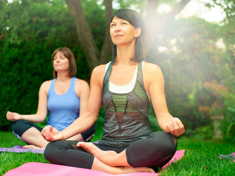 Yoga instructor teaching a class of mature women high