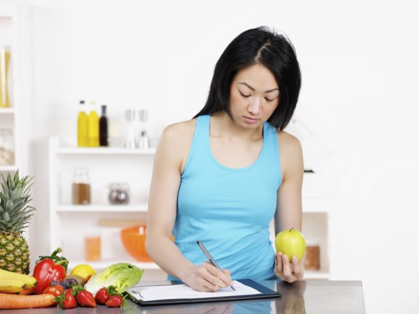 Asian female Nutritionist documenting diet plan.