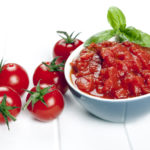 Diced and whole tomatoes. garnished with basil.Diced and whole tomatoes, with olive oil behind.  Garnished with basil.