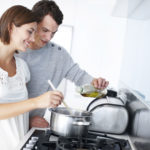 A happy young couple preparing a meal together in the kitchen