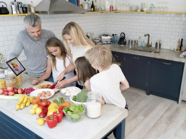 Family cooking dinner together at home and looking very happy. Design  on tablet is own design.
