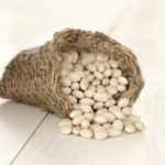 Close up white beans on white wooden table. Macro shoot with selective focus. Shallow DOF