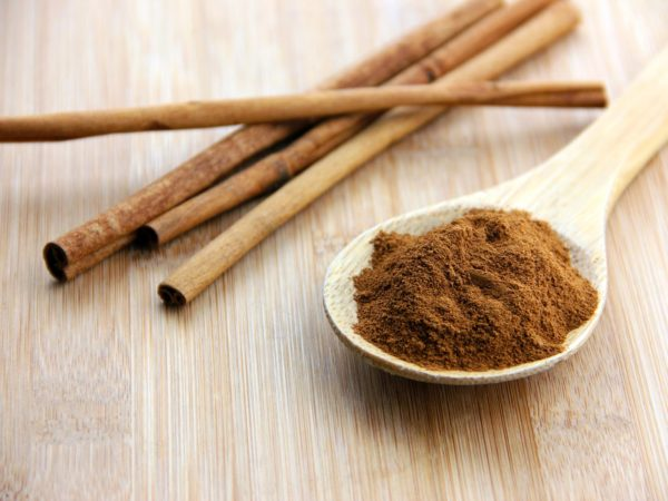 A spoonful of cinnamon and cinnamon sticks set on a bamboo wooden surface