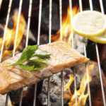Top view grilled salmon with lemon on the flaming grill