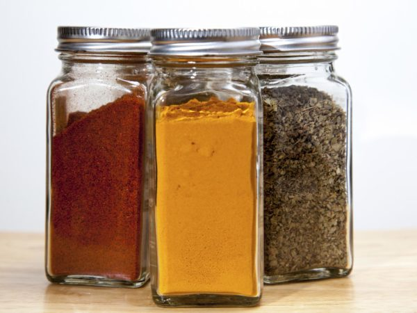 Cayenne pepper, turmeric & Coriander spices in square jars.