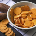 Raw sweet potato with at the vintage wooden table, in the bowl and a towel