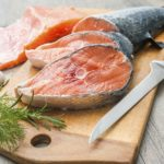 Raw salmon fish steaks with fresh herbs on cutting board, high cholesterol