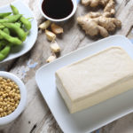 A block of tofu with a bowl of edamame, a bowl of soy beans, garlic cloves,soy sauce, and ginger root.