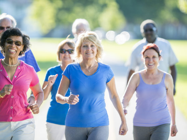 A multi-ethnic group of senior adults are exercising together by walking in the park on a sunny day.