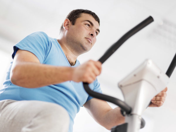 Low angle view of young serious overweight man cycling on exercise bike.