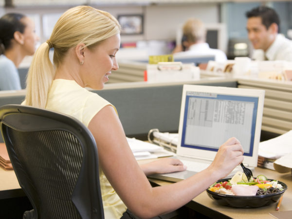 Businesswoman using laptop and eating salad