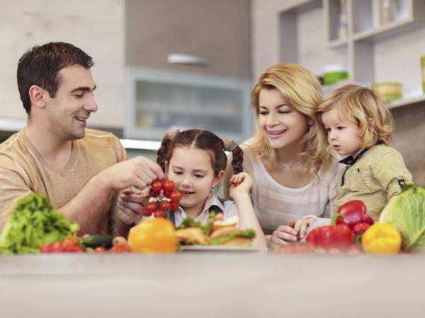 Happy family in the kitchen holding healthy food.