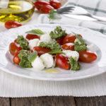 Caprese. Italian salad - mozzarella, tomato, basil, pesto.