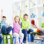 """Portrait of an cute children talking about vegetable in a preschool, selective focus to children with arms raised guessing, teacher learning children about vegetable. Holding paprika."""