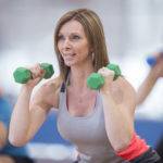 A group of adults are taking a fitness class together at the gym. They are using dumbbell weights to workout their arms.
