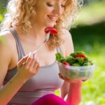 Young slim woman holding a bowl of fresh salad ofter working out outdoors in the park. Eating on fresh air, sitting on the grass and enjoying early morning. Healthy lifestyle.