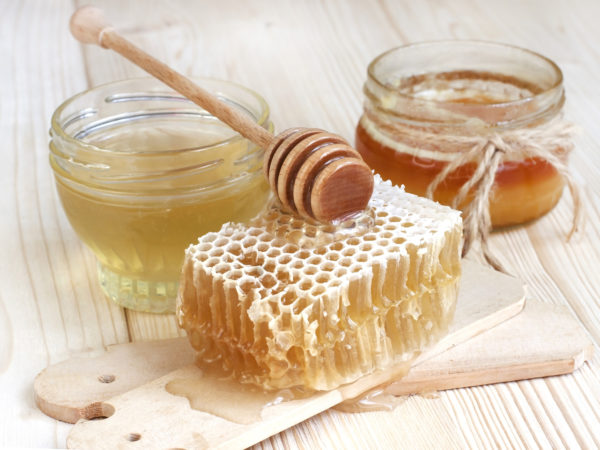 Glass cans full of honey on  wooden table