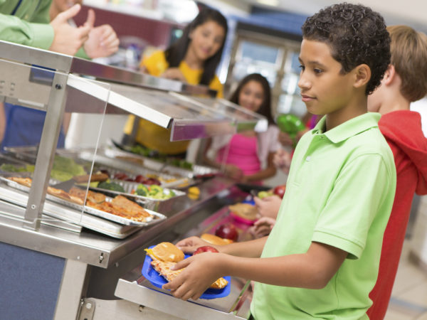 Middle school students getting lunch items in cafeteria line.