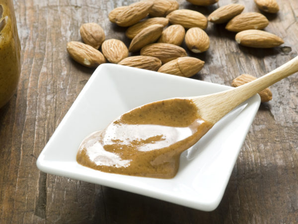 A dish of homemade almond butter on rustic wood surface.  Whole almonds in background and wooden spoon with fresh almond butter in foreground.