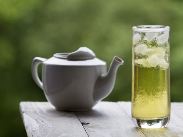 With long green ice tea and glass teapot on unfocused background