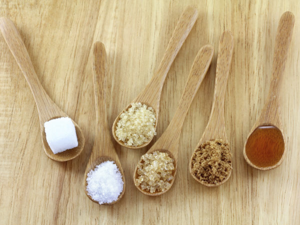 Spoons of different types of sugar on the wooden background