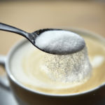 Sprinkling refined sugar from a spoon into a cup of coffee