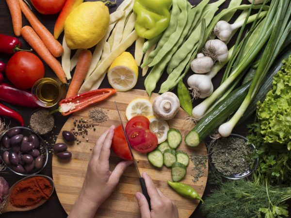 Human hands cutting raw vegetables on a cutting board and vegetables and spices around