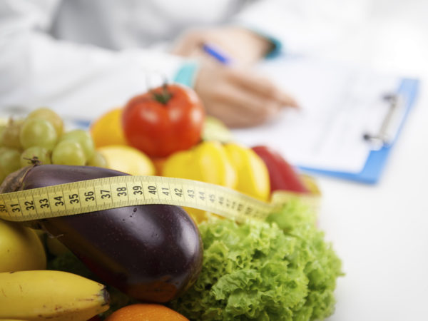 Healthy nutrition concept. Close-up of fresh vegetables and fruits with measuring tape lying on doctor&#039&#x3B;s desk.