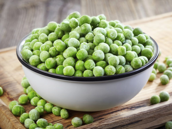 bowl of frozen green peas on wooden table