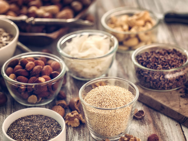 Superfoods in Bowls like chia, quinoa, cocoa, almonds and cashew on wooden background.