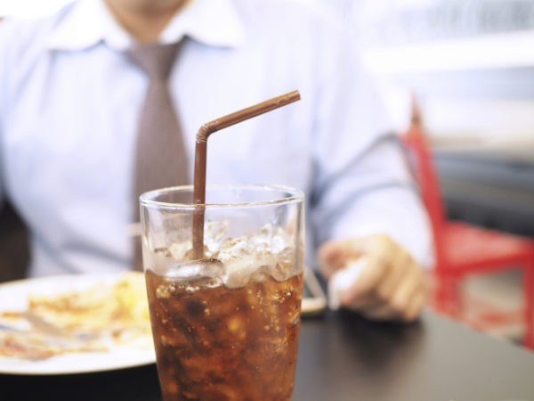 Fat and unhealthy businessman having soft drink and junk food (focus on soft drink, blurred out the rest) - unhealthy and junk food concept