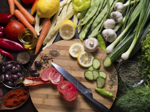 Photo from directly above of a kitchen knife and sliced vegetables on a cutting board and variation of vegetables and spices around.