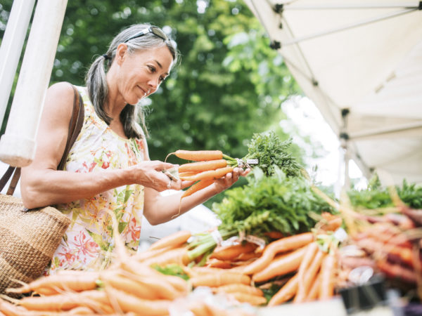 An older woman in her fifties shopping in a local farmers market with fresh, organic vegetables. She smiles as she chooses carrots. Horizontal image with copy space.