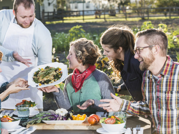 A group of people sitting outdoors at a dining table, being served locally grown food.  The chef or waiter is standing, presenting a dish of beautifully prepared vegetables.  This image represents the farm-to- table-or-farm to fork movement.