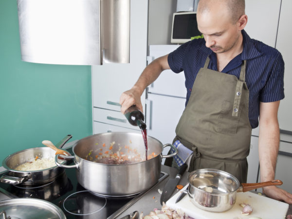 Mid adult caucasian man cooking with wine at home.