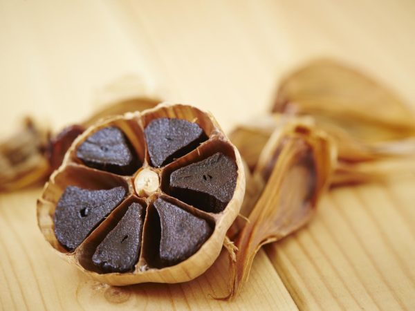 Black garlic on dish, wooden background