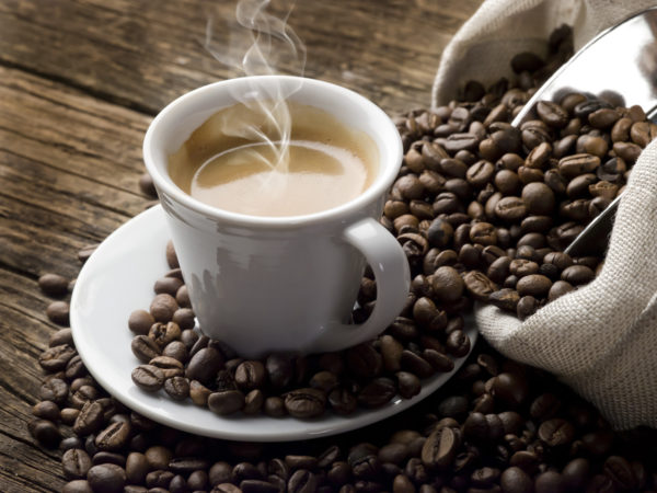 Steaming hot coffee in a small white coffee cup sits on a round saucer and is surrounded by coffee beans.  A sack of coffee beans with a shiny metal coffee scooper sticking out of it is visible along the right side of the image.  Beans are spilling from the sack onto the saucer and the brown wooden table beneath it.