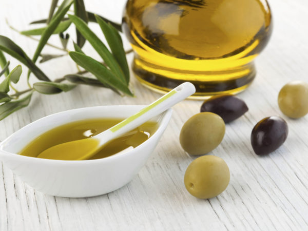 Olive oil and green and black olives on white wooden background