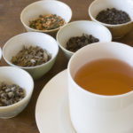 Selection of dried tea leaves from around the world and a cup of hot brewed tea, ready for comparative tasting and sipping. The white saucer holds a full pour of the beverage. Chinese, Japanese, and Indian varieties such as oolong, jasmine, darjeeling, and other black and green choices are shown.