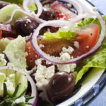 Close-up of bowl of Greek salad.  Luscious vine-ripened tomatoes, with feta cheese, kalamata olives, cucumber, red onion, kos lettuce and rosemary.  More salads: