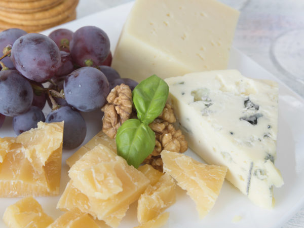 Different varieties of cheese, walnuts, red grapes and basil leaves