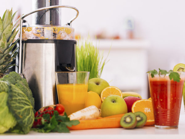 Making a healthy drink with fruit and vegetables by using an electric juicer