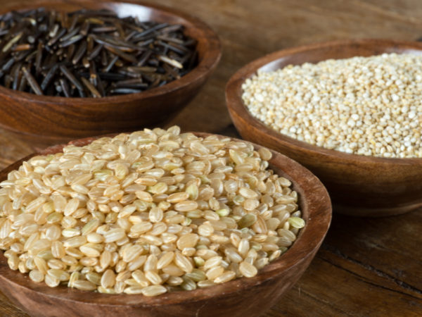 Small wood bowls filled with brown rice, quinoa and wild rice. This is shot on a wood table.