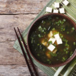 Japanese miso soup in a brown bowl on the table. horizontal view from above