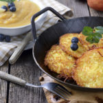 Homemade and crispy fried potato pancakes served in an iron pan with apple sauce