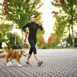Young woman walking her don in a neighborhood with houses and trees in the background.
