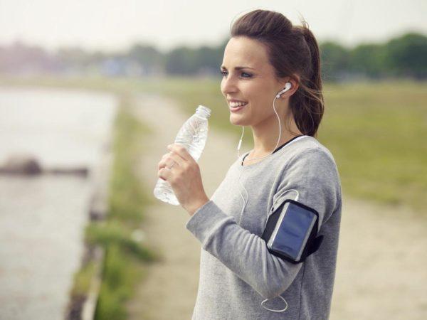 Female runner smiling while drinking bottled water
